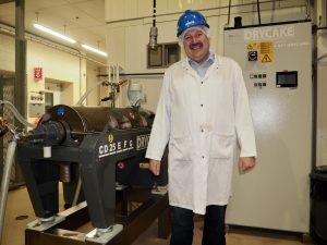 Ken Gossen in front of decanter centrifuge at FPDC in Leduc, Alberta. Photo by Therese Kehler